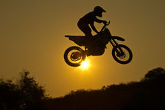 Motorcross Jumping. Status of silhouate motocross jumping over the amber light of sunset background Royalty Free Stock Image