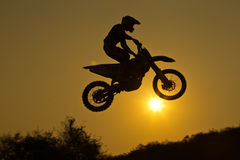 Motorcross Jumping. Status of silhouate motocross jumping over the amber light of sunset background Royalty Free Stock Photos