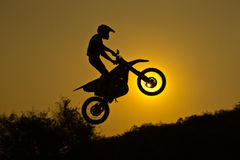 Motorcross Jumping. Status of silhouate motocross jumping over the amber light of sunset background Stock Photo