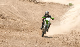 Motorcross race. Motorcross athlete with his bike on a mud road increasing speed Stock Image