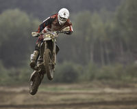 Motorcross rider. Motorcyclist on an off-road motorcycle flying through the air after riding over a jump royalty free stock image