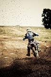 Motorcross rider. Going through a turn shooting up mud, slightly out of DOF, focus is on the flying debris Stock Image
