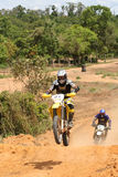 Motorcross Rider on Motorcycle In Race. Two motorcross riders in a race coming to jump section of the race track Stock Photo
