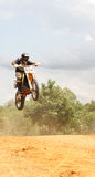 Motorcross Rider In A Race. A motorcross rider in a race, at a jump on the course Royalty Free Stock Photos