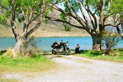 Motorcyce rider near lake stock photography