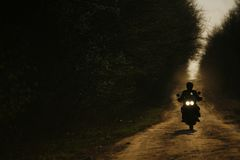 Motorcycle. A motorcycle and its rider are silhouetted on an off-road track in Romania Royalty Free Stock Image