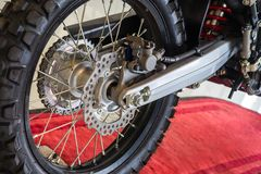 Motorcycle Alloy wheels and tire complete with disk braking system on red carpet foor . stock photo
