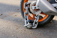 Motorcycle anti-theft chain with padlock security lock on rear w Royalty Free Stock Photography