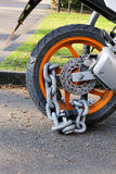Motorcycle anti-theft chain with padlock security lock on rear w Stock Photo