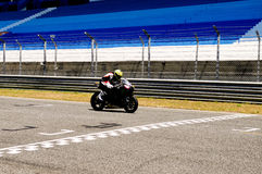 Black Motorcycle Arriving Finish Line, Victory, Motor Sports. Motorcycle arriving finish line marking. Empty stands from Estoril Circuit Stock Image