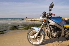 Motorcycle at the beach. Motorcycle standing on the beach near the sea Royalty Free Stock Photos