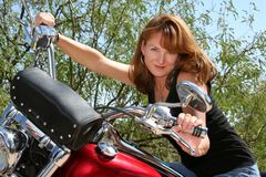 Motorcycle beauty. Pretty strawberry blonde woman on motorcycle stock image