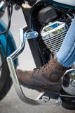 Motorcycle boot on the footboard of motorcycle, close-up Stock Photos