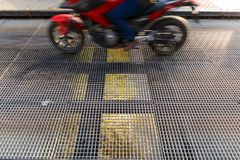 Motorcycle circulating on a bridge with metal grid floor. Over Pisuerga River on Valladolid, Spain Royalty Free Stock Photos
