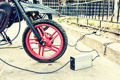 Motorcycle. Close-up of an electric motorcycle charging, e-bike, is charged with current and then inserted into the bike, green ecology royalty free stock image