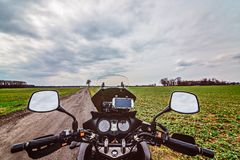 Motorcycle cockpit at the dirt road. Royalty Free Stock Photography
