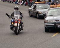 Motorcycle Cop. Sheriff on motorcycle along with two patrol cars at a parade stock photos