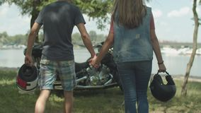 Motorcycle couple holding helmets in hands walking stock video footage