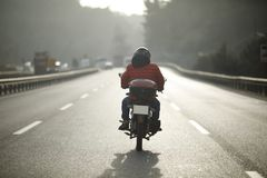 Motorcycle Courier On The Highway Stock Photos