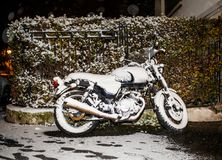 Motorcycle covered with snow at night parked near house Royalty Free Stock Images