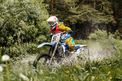 Motorcycle crosses puddles of water and mud in forest Royalty Free Stock Photo