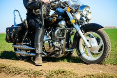 Motorcycle Driver on the Custom Chopper Bike on Autumn Dirt Road in the Green Field. Adventure Concept. Motorcycle Driver on the Custom Chopper Bike on the royalty free stock photography