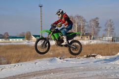 Motorcycle driver flies over hill out of snow Royalty Free Stock Images