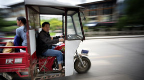 Motorcycle driver. Panning image of motorcycle driver passing thru in yangshuo town in china royalty free stock photo