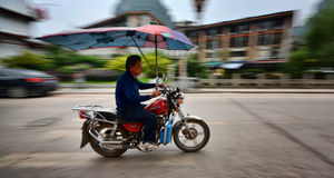 Motorcycle driver. Panning image of motorcycle driver passing thru in yangshuo town in china royalty free stock photos