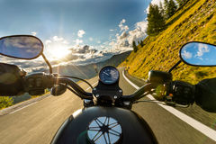Motorcycle driver riding in Alpine highway, handlebars view, Austria, Europe. Motorcycle driver riding in Alpine highway, handlebars view, Austria, central Stock Images