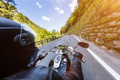Motorcycle driver riding in Alpine highway, handlebars view, Austria, Europe. Motorcycle driver riding in Alpine highway, handlebars view, Austria, central Stock Photo
