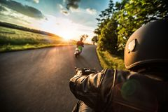 Motorcycle driver riding in Alpine highway, handlebars view, Austria, Europe. stock photo