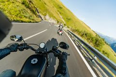 Motorcycle driver riding in Alpine highway, handlebars view, Austria, Europe. royalty free stock images