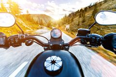 Motorcycle driver riding in Alpine highway, handlebars view, Austria, Europe. Motorcycle driver riding in Alpine highway, handlebars view, Austria, central Stock Photography