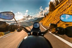 Motorcycle driver riding in Alpine highway, handlebars view, Austria, Europe. Motorcycle driver riding in Alpine highway, handlebars view, Austria, central Royalty Free Stock Photos