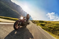 Motorcycle driver riding in Alpine highway. Outdoor photography. Motorcycle driver riding in Alpine highway,  Hochalpenstrasse, Austria, Europe. Outdoor Royalty Free Stock Photos