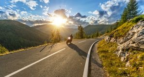 Motorcycle driver riding in Alpine highway. Outdoor photography. Motorcycle driver riding in Alpine highway, Nockalmstrasse, Austria, Europe. Outdoor photography royalty free stock image