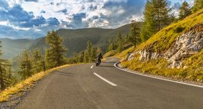 Motorcycle driver riding in Alpine highway. Outdoor photography. Motorcycle driver riding in Alpine highway, Nockalmstrasse, Austria, Europe. Outdoor photography stock image