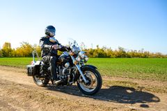 Motorcycle Driver Riding Custom Chopper Bike on Autumn Dirt Road in the Green Field. Adventure Concept. Motorcycle Driver Riding Custom Chopper Bike on an royalty free stock photography