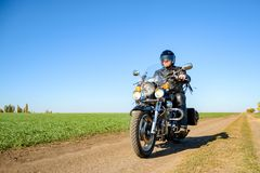 Motorcycle Driver Riding Custom Chopper Bike on Autumn Dirt Road in the Green Field. Adventure Concept. Motorcycle Driver Riding Custom Chopper Bike on an royalty free stock photos