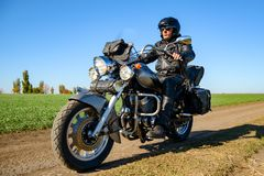 Motorcycle Driver Riding Custom Chopper Bike on Autumn Dirt Road in the Green Field. Adventure Concept. Motorcycle Driver Riding Custom Chopper Bike on an stock photos