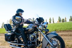 Motorcycle Driver Riding Custom Chopper Bike on Autumn Dirt Road in the Green Field. Adventure Concept. Motorcycle Driver Riding Custom Chopper Bike on an stock photography