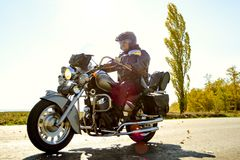 Motorcycle Driver Riding Custom Chopper Bike on Autumn highway. Adventure Concept. Motorcycle Driver Riding Custom Chopper Bike on an Autumn highway. Adventure stock photos