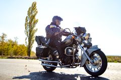 Motorcycle Driver Riding Custom Chopper Bike on Autumn highway. Adventure Concept. Motorcycle Driver Riding Custom Chopper Bike on an Autumn highway. Adventure royalty free stock photos