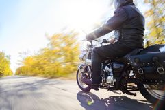 Motorcycle Driver Riding Custom Chopper Bike on Autumn Road. Travel and Adventure Concept. Motorcycle Driver Riding Custom Chopper Bike on an Autumn Road. Travel stock photo