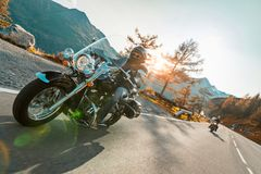 Motorcycle driver riding japanese high power cruiser in Alpine highway on famous Hochalpenstrasse, Austria. Motorcycle driver riding japanese high power cruiser Stock Images