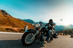 Motorcycle driver riding japanese high power cruiser in Alpine highway on famous Hochalpenstrasse, Austria. Royalty Free Stock Photography