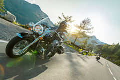 Motorcycle driver riding japanese high power cruiser in Alpine highway on famous Hochalpenstrasse, Austria. Royalty Free Stock Photos