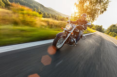 Motorcycle driver riding on motorway. In beautiful sunset light in blur motion effect. Shot from front view royalty free stock photos