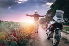 Motorcycle driver stands with his arms outstretched. for a meeting of adventures on the dirt road sunset time, enduro, off road, stock photo